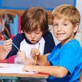 Kinder, die Bilder im Kindergarten malen Lizenzfreies Stockfoto