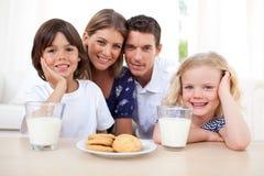 Kinder, die Biskuite und Trinkmilch essen stockbilder