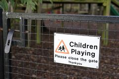 Kinder, die bitte draußen nahes Tor-Zeichen am Spielplatz-Park spielen stockfoto