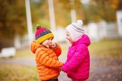 Kinder, die Blätter im schönen Herbsttag werfen stockbild