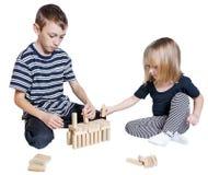 Kinder, die Blöcke Jenga lokalisiert auf weißem Hintergrund spielen Lizenzfreie Stockfotos