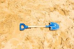 Kinder, die blaue Schaufel der Werkzeuge auf Strand spielen stockbild