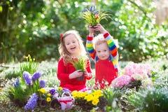 Kinder, die Blumen in blühendem Garten pflanzen lizenzfreies stockbild