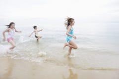 Kinder, die in Brandung am Strand laufen Lizenzfreie Stockbilder