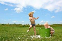Kinder, die in Bubbley-Wasser spielen stockbilder