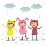 Kinder, die bunte Regenmäntel tragen und Stiefel, die am regnerischen Tag spielen Stockbild