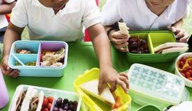 Kinder, die das Mittagessen an der Volksschule essen stockfotografie