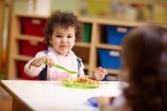 Kinder, die das Mittagessen im Kindergarten essen Lizenzfreie Stockfotos