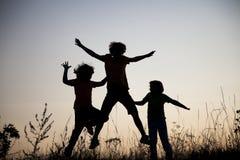 Kinder, die das Springen auf die Sommersonnenuntergangwiese silhouettiert spielen lizenzfreies stockfoto