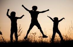 Kinder, die das Springen auf die Sommersonnenuntergangwiese silhouettiert spielen stockbilder