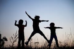 Kinder, die das Springen auf die Sommersonnenuntergangwiese silhouettiert spielen lizenzfreies stockbild