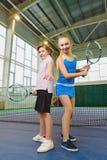 Kinder, die das Tennis und Aufstellung Innen spielen Stockbilder