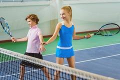 Kinder, die das Tennis und Aufstellung Innen spielen Stockfotografie