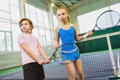 Kinder, die das Tennis und Aufstellung Innen spielen Lizenzfreie Stockfotos