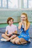 Kinder, die das Tennis und Aufstellung Innen spielen Stockfoto