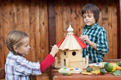 Kinder, die das Vogelhaus für den Winter malen Lizenzfreie Stockfotos
