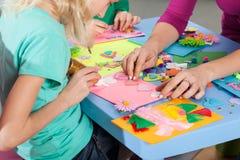 Kinder, die Dekorationen auf Papier machen Stockfoto