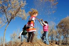 Kinder, die in den Blättern spielen Stockfotos
