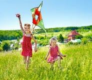 Kinder, die den Drachen im Freien fliegen. lizenzfreie stockbilder