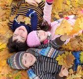 Kinder, die in den Fallblättern liegen Lizenzfreie Stockfotos