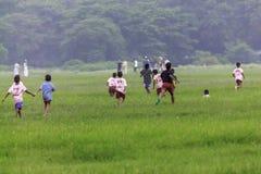 Kinder, die in den Park des Frühlingsfeldes in der zufälligen Kleidung laufen stockfotos