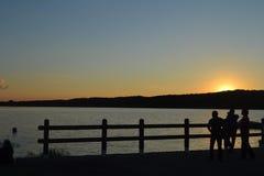 Kinder, die den Sonnenuntergang über dem Hügel aufpassen Stockbild