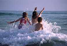 Kinder, die in den Wellen spielen stockfotografie