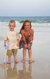 Kinder, die in der Brandung auf einem Strand spielen Stockbilder
