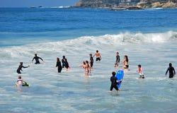 Kinder, die in der Brandung des schläfrigen hohlen Strandes im Laguna Beach, Kalifornien spielen Lizenzfreie Stockfotografie
