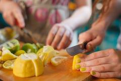Kinder, die an der Küche kochen Hände, die frische organische Zitronen auf dem Holztisch schneiden Fruchtsnack stockfotografie