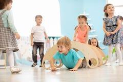 Kinder, die in der Kindergarten- oder Kindertagesst?ttenmitte spielen stockfotos