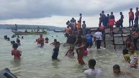Kinder, die in der Kleidung durch Strand auf Mansinam schwimmen stock footage