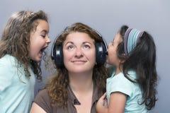 Kinder, die an der Mutter während sie hörend Musik schreien Stockbilder