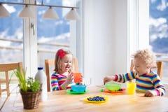 Kinder, die in der sonnigen Küche frühstücken lizenzfreies stockfoto