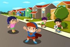 Kinder, die in der Straße einer Vorstadtnachbarschaft spielen Stockfotos