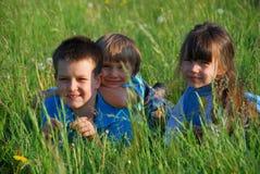 Kinder, die in der Wiese sich entspannen Stockbild