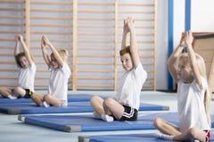 Kinder, die in der Yogahaltung sitzen stockfotografie