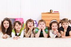 Kinder, die in der Zeile liegen stockbild