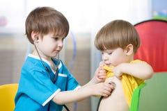 Kinder, die Doktor im Spielzimmer oder im Kindergarten spielen stockfotografie