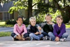 Kinder, die draußen in einer Reihe sitzen Lizenzfreie Stockfotos