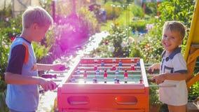 Kinder, die draußen Tischfußball spielen Spaß draußen Lizenzfreie Stockfotos