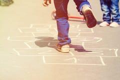 Kinder, die draußen Hopse auf Spielplatz spielen Stockfotografie