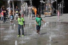 Kinder, die durch Brunnen laufen Lizenzfreie Stockfotos