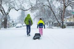 Kinder, die durch eine schneebedeckte Nachbarschaft mit einem Schlitten gehen Lizenzfreies Stockfoto