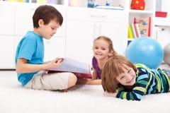 Kinder, die ein Buch lesen und Spaß haben stockfotografie