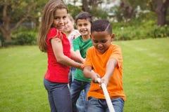 Kinder, die ein großes Seil ziehen Stockfoto