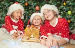 Kinder, die ein Lebkuchenhaus verzieren Stockbilder