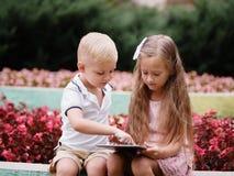 Kinder, die eine digitale Tablette lernen und im Park sitzen Ein Junge und ein Mädchen, die in einem Gerät auf einem natürlichen  stockfoto