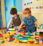 Kinder, die eine Wand der Plastikblöcke aufbauen Stockfoto