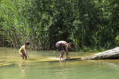 Kinder, die in einem Fluss spielen stockbild